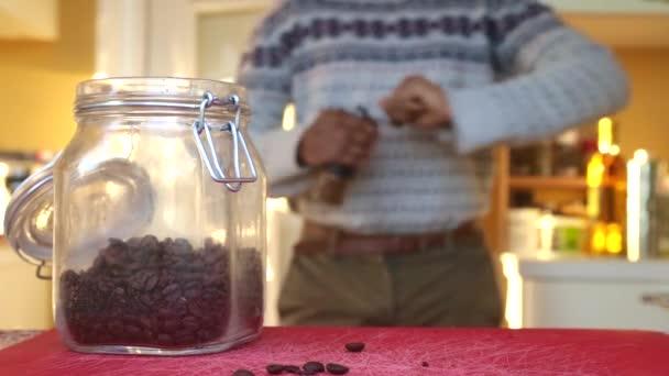 Mann mahlt zu Hause geröstete Kaffeebohnen manuell
