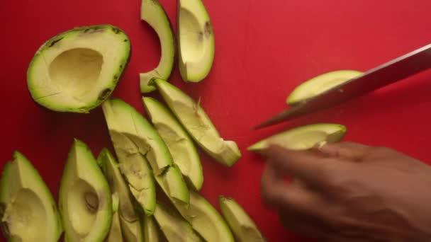 Az avokádó vágódeszkán történő elkészítését végző személyek kezeinek felső nézete