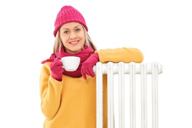 Joyful woman leaning on a radiator and holding a cup