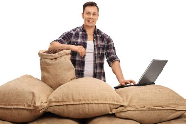 agricultural worker posing with burlap sacks and laptop