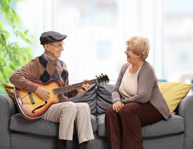Elderly man playing a guitar to an elderly