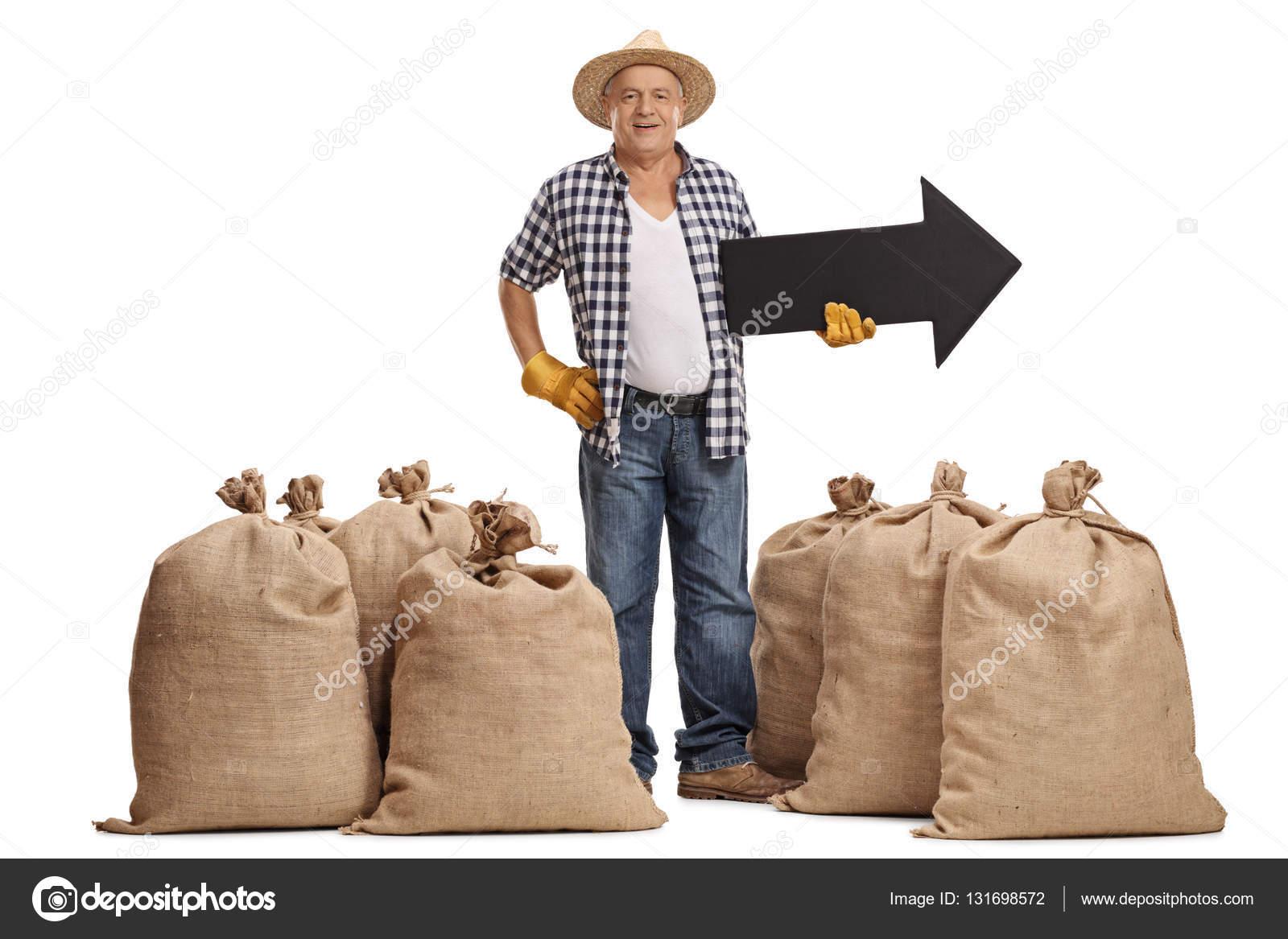 Retrato de longitud completa de un anciano agricultor entre sacos de  arpillera y sosteniendo una flecha hacia derecha aislada sobre fondo blanco  — Foto de ... 17f5b2e8db6