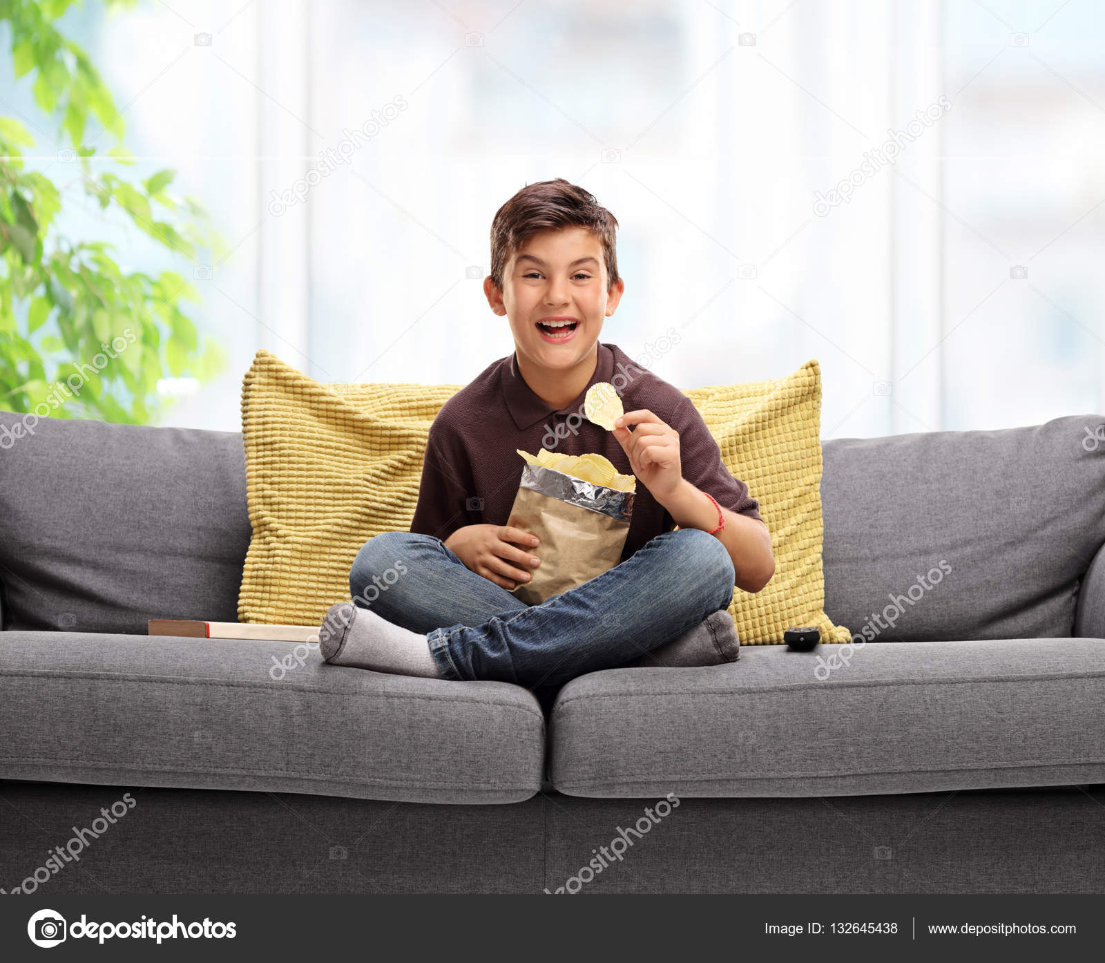 Boy Sitting On A Sofa And Eating Potato Chips Stock Photo