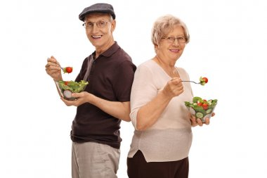 Mature man and woman eating salads