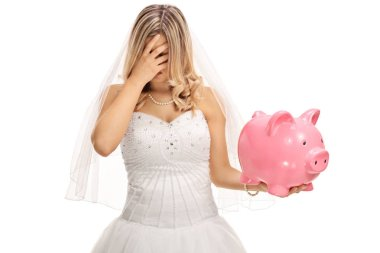 Disappointed bride holding a piggybank