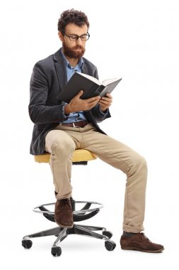 Man sitting on a chair and reading a book