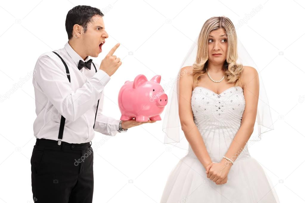 Angry groom holding a piggybank and scolding an embarrassed brid