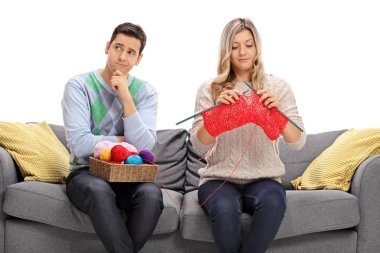 Bored guy sitting on a couch next to a woman knitting