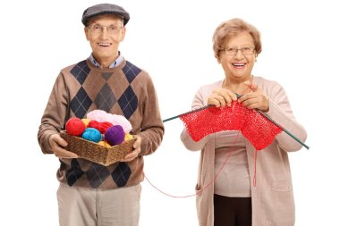 Elderly man helping an elderly woman knit