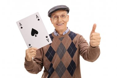 Senior holding ace of spades card and making thumb up sign