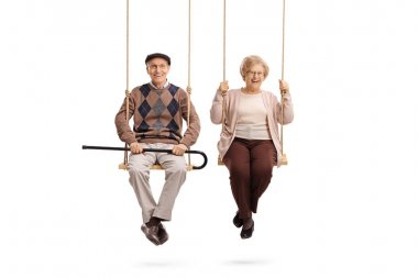 Elderly man and an elderly woman sitting on swings