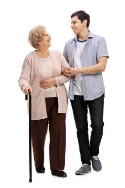 man helping a mature woman with a walking cane