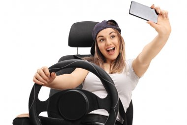 Cheerful girl sitting in car seat and taking selfie