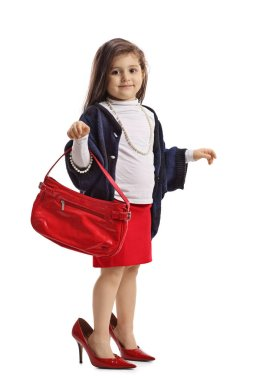 Little girl in oversized high heels holding a handbag