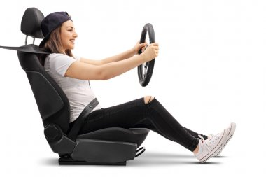 Teenage girl sitting in car seat and holding steering wheel