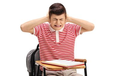 Teen student sitting in a chair and covering his ears