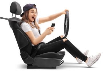 Teenage girl driving and looking at her phone