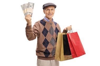elderly man holding money bundles and shopping bags