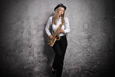 Attractive young woman playing a saxophone