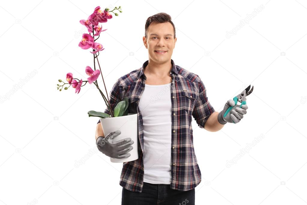 Gardener with an orchid plant and garden shears