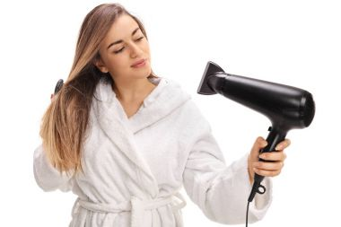 Girl in a bathrobe blowing her hair with a hairdryer