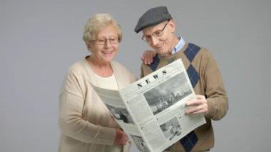 Seniors reading a newspaper