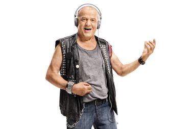 Elderly punker wearing headphones and playing air guitar