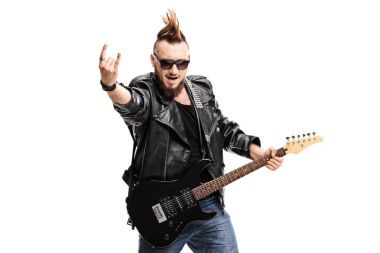 Punker with an electric guitar making a rock hand gesture