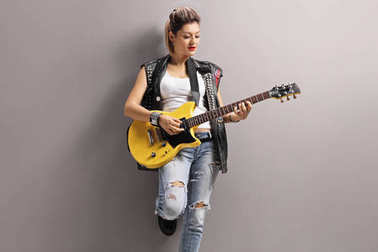 Female punker playing an electric guitar