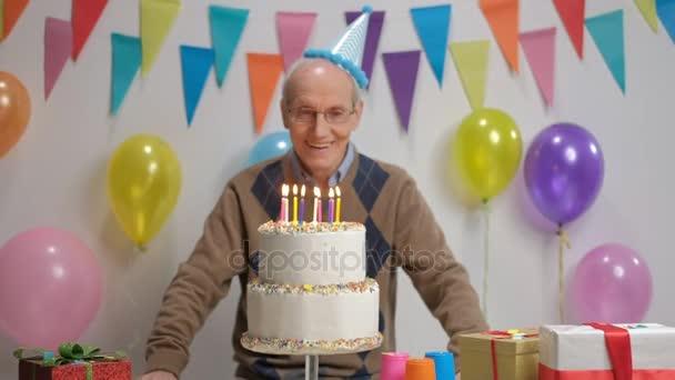 Senior fúj gyertyákat születésnapi torta dekoráció zászlókkal és léggömbök a falhoz