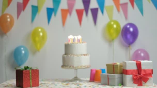Narozeninový dort s hořící svíčky proti zdi s vlajkami dekorace a balonky