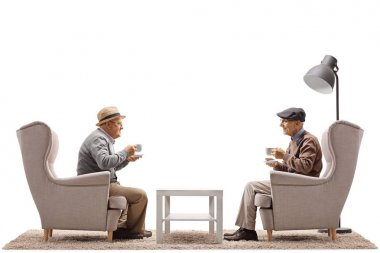 Elderly men with cups sitting in armchairs