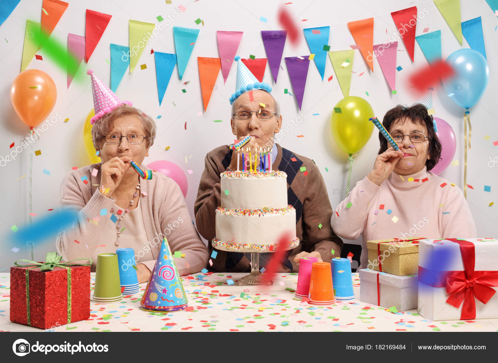 Seniors Celebrating Birthday Cake Party Horns Stock Photo
