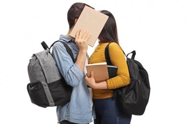 Teen students kissing behind a book