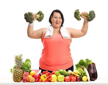 Overweight woman exercising with broccoli dumbbells behind a table with fruit and vegetables isolated on white background