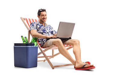 Tourist with a laptop sitting in a deck chair next to a cooling box isolated on white background