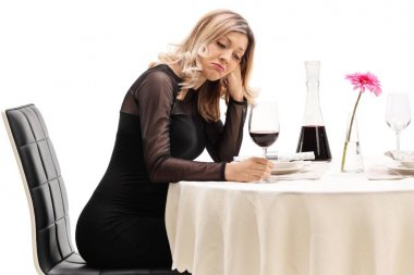 Lonely young woman sitting at a restaurant table isolated on white background
