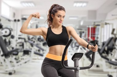 Fitness woman riding an exercise bike and flexing her biceps in a gym