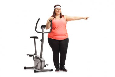Full length portrait of an overweight woman leaning on an exercise bike and pointing isolated on white background
