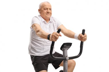 Mature man with earphones riding an exercise bike isolated on white background