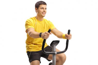 Young guy with headphones exercising on a stationary bike isolated on white background