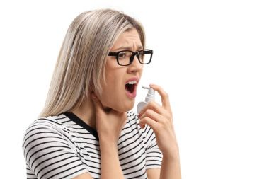 Young woman with a sore throat using a mouth spray isolated on white background