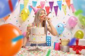 Fényképek Fiatal nő, egy születésnapi torta fúj egy fél horn a falhoz léggömb és dekorációs zászlók