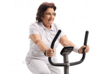 Mature woman listening to music and exercising on a stationary bike isolated on white background