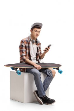 Teenage skater with a phone and a longboard sitting on a cube isolated on white background