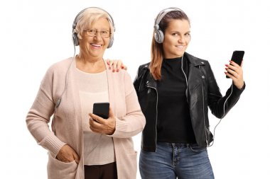 Cool grandmother and granddaughter listening to music on headpho