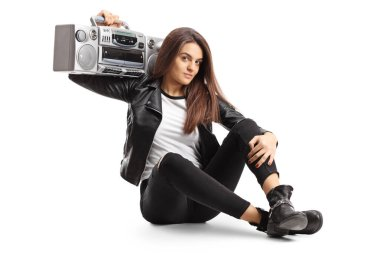 Young female sitting on ground and holding a boombox radio on he