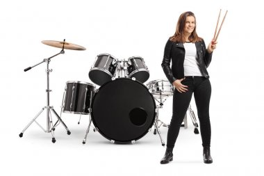Young female posing with a drum set and holding drumsticks