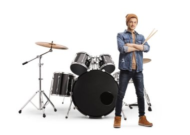 Guy in casual clothes holding drumsticks and posing with a drum
