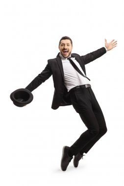 Man in a suit dancing and holding a fedora hat